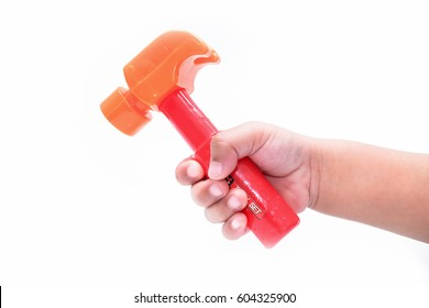 Child's hand holding a Toy Hammer, isolated on a white background