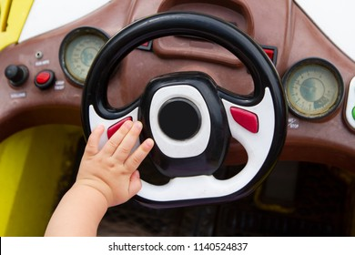 The child's hand holds the handle of the car. The wheel of a child car in the child's hand.