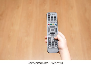 The child's hand holds the TV remote control on wooden floor background