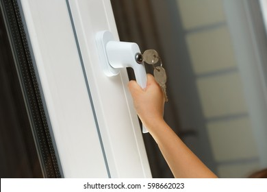 Child's hand on secure window handle with key