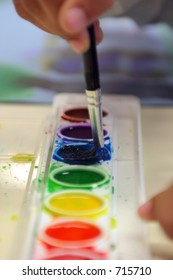 Child's Hand Painting A Watercolor Picture
