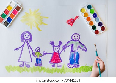 The child's hand paints a happy family with brush of watercolor on a white sheet of paper. The top view