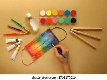 La mano de un niño pinta una máscara protectora en colores arcoiris junto a la papelería escolar y antiséptico en el fondo amarillo. De vuelta a la escuela 2020 y protección contra el coronavirus y otras infecciones.