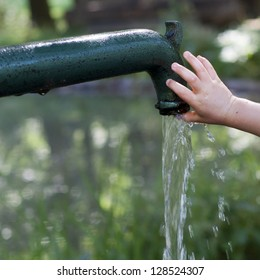 Child's hand playing with drinking water running  from an old  water pump; aid concept. .