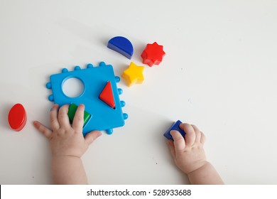 Child's hand, playing with montessori toys.