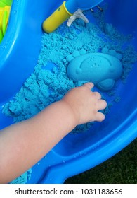 The child's hand plays kinetic sand