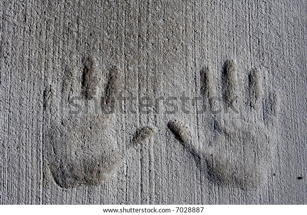 Child's hand prints pressed into cement sidewalk.