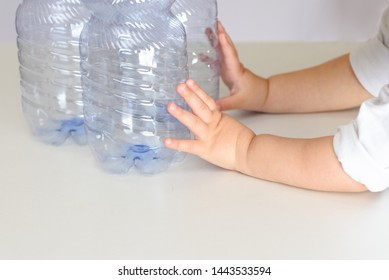 Child's hand push the plastic bottles. Conceptual image for anti plastic campain. Concept of awareness of the plastic pollution world, the future for our children.