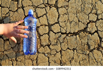 Child's hand reaches a bottle of water lying on dry cracked soil. Concept of the consequences of global warming.
