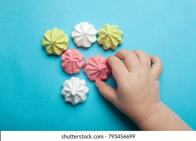 A child's hand reaches for the sweet airy, multi-colored meringue on a blue background. The concept of a holiday, a child's birthday.