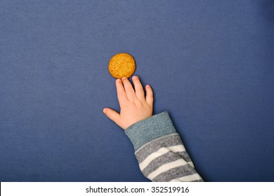 Child's hand reaching for cookie on the table. Baby taking a food.