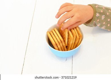 Child's hand reaching out to take cookies from the plate