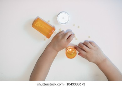 A child's hand is reaching for prescription drugs on an isolated white background with room for text. He is holding the pills from the prescription bottle, potentially dangerous and fatal.