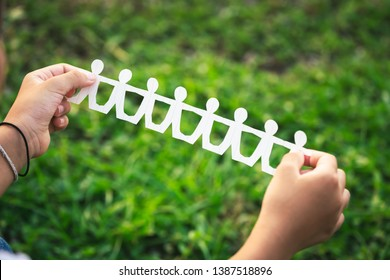 Child's hand show the success of cutting paper as a human chain doll over the green field in the park, Teamwork or CSR concept
