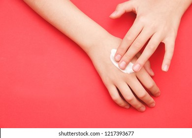 the child's hand smeared her hand with cosmetic cream lotion with a copy of space on a red background of minimalism. The concept of women's pattern blog.