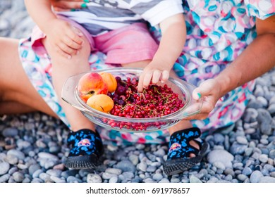 Child's hand takes fresh berries and fruits in the open air