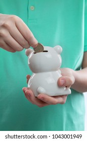 child's hand throwing a coin into a white porcelain piggy Bank