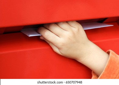 The child's hand throws a letter into the mailbox
