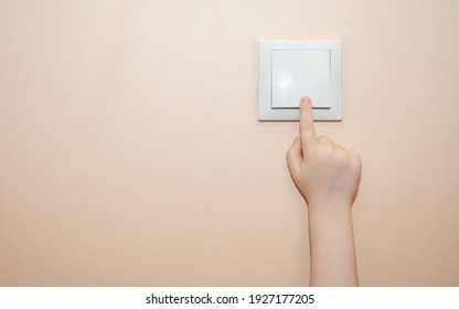 the child's hand turns off the light .