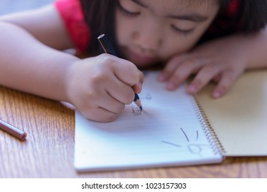 The child's hands with colored pencils drawing or writing on notebook. Education and children activities concept.