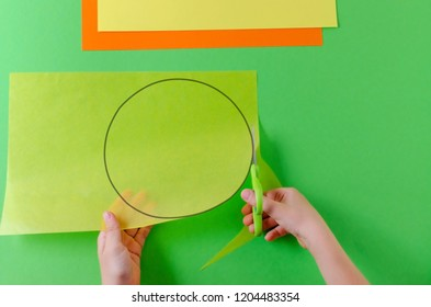 child's hands cut circle on transparent paper with scissors, top view, on green