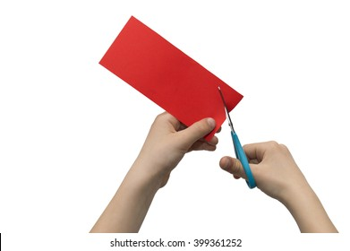 Child's hands cutting colored red paper with scissors isolated on white background