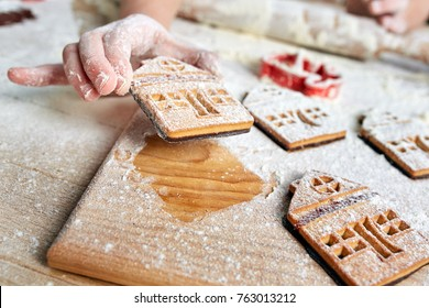 Child's hands decorate traditional Christmas cookies. Cooking on kitchen table