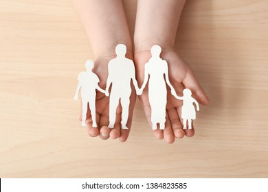 Child's hands with figure of family on light background. Concept of adoption