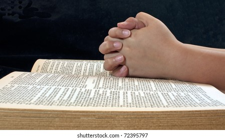 A child's hands folded on an open Bible