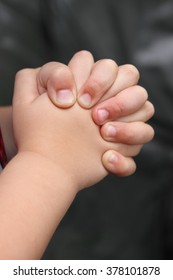 A child's hands folded in prayer