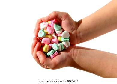A child's hands full of candy hearts.