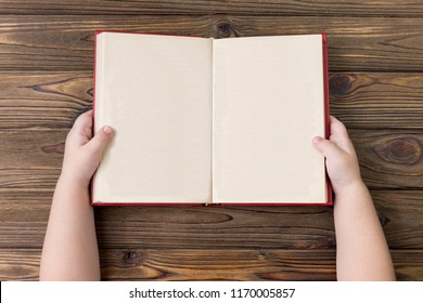 The child's hands hold an open book with clean sheets of pages. On a wooden background. mock up. The concept of reading books, education, school.