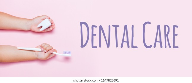 Child's hands holding big tooth and toothbrush on pink backgroubd. Healty care teeth concept. Top view, flat lay. Dental care text