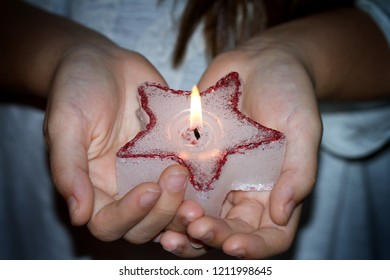 Child's hands holding candle christmas star in night sign of hope concept