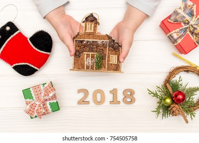 Child's hands holding christmas decorative wooden house near gift boxes on white background. Flat lay, top view