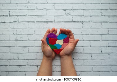Child's hands holding a heart on white background with text space. World autism awareness day.