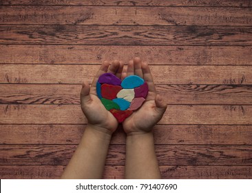 Child's hands holding a multicolored heart on wooden background with text space. World autism awareness day.