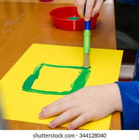 Child's hands holding paint brush painting square on yellow paper sitting at wooden table