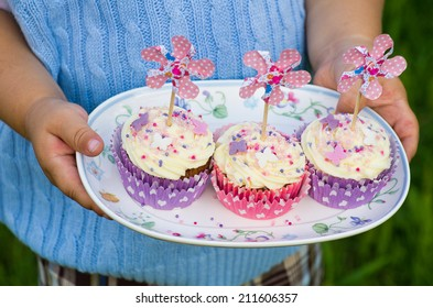 Child's hands holding a plate with pink and purple cupcakes with pinwheels