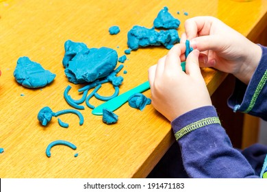 A Childs hands holding Play Doh
