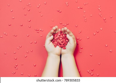 Child's hands holding red hearts on red background. top view, flat lay. St. Valentine's comcept.