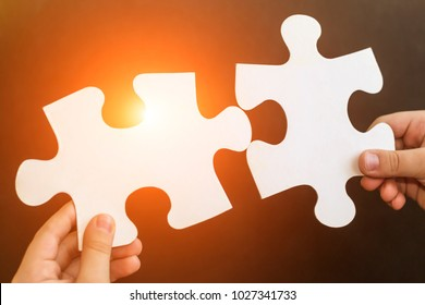 Child's hands holding two big puzzle pieces. Baby connecting jigsaw puzzle. Close up. Education, business, learning, family concept.