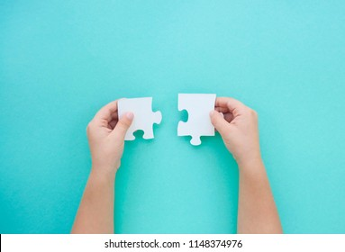 Child's hands holding two puzzle pieces on blue background as a symbol of autism awareness.