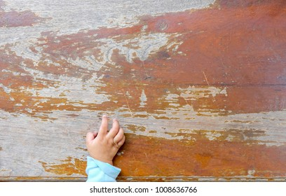 Child's hands located on brown old wooden boards background