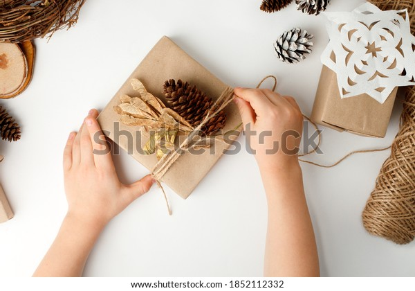 Child's hands making Christmas gift. Flat lay, top view, Kid hands wrapped gift box in craft paper, natural decoration details, zero waste packaging on white table. Eco-friendly concept