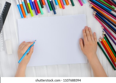 The child's hands are painted with colored pencils on a white sheet of paper on a wooden table.