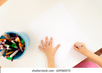 Child's hands with pencil view from above