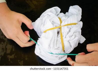 A child's hands preparing a t-shirt for tie-dye design