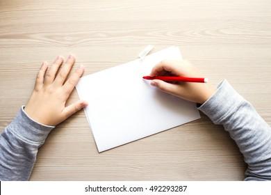 Les mains de l'enfant avec un bout de feutre rouge sur la table en bois avec un morceau de papier. Vue de dessus.