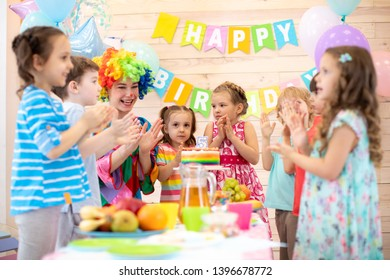 Childs are happy after they have blowed candles out on birthday party. Kids with clown clap their hands